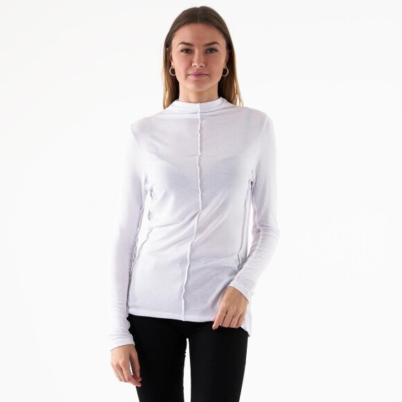 Image of   Mock neck exposed seam top